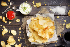Potato chips with dipping sauces on a rustic table Stock Photos