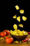 Potato chips fall into a clay bowl isolated on a black backgroun Stock Photo