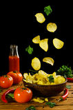 Potato chips fall into a clay bowl isolated on a black backgroun Royalty Free Stock Image