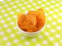Potato chips falling in the white plate Royalty Free Stock Image