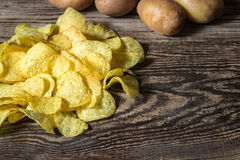Potato chips. Fresh raw potatoes. Potato chips on a wooden table. Fresh raw potatoes on the background Stock Photo