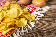 Potato chips. Fresh raw potatoes. Potato chips on a wooden table. Fresh raw potatoes on the background Royalty Free Stock Photography