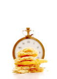 Potato chips in front of vintage pocket clock. time and food concept Stock Photos