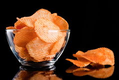 Potato chips in glass bowl, isolated on background Royalty Free Stock Images