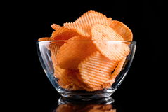 Potato chips in glass bowl, isolated on background Stock Photos