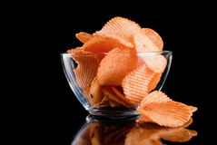 Potato chips in glass bowl, isolated on background Stock Image