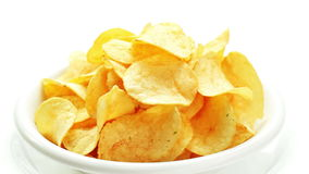 Potato chips heap rotating on a white plate stock video footage