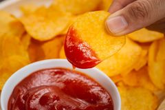 Potato chips and ketchup. Beer snack, unhealthy eating.  royalty free stock photography