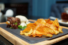 Potato chips and meat on table Royalty Free Stock Photography