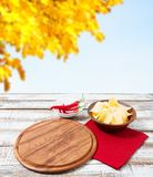 Potato chips, napkin,red pepper on wooden table on blurred yellow autumn background.Pizza desk.Tablecloth holiday concept.  stock photography