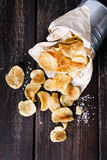Potato chips over dark wooden background Stock Image
