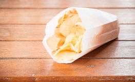 Potato chips in paper bag on table Royalty Free Stock Photo