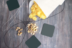 Potato chips in paper cone, roasted and salted pistachios, coasters. Royalty Free Stock Images