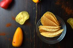 Potato chips with paprika on dark wooden background Stock Photo
