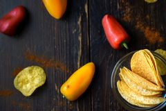 Potato chips with paprika on dark wooden background Royalty Free Stock Photography