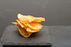 Potato chips. Potato chips piled on a gray slate snack plate Royalty Free Stock Images