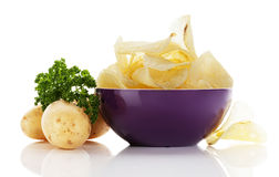 Potato chips with potatoes and parsley Stock Images
