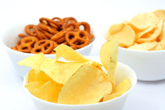 Potato chips and pretzels. Potato chips, corn chips and pretzels in bowls, isolated on white Royalty Free Stock Images