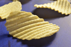 Potato chips with ridged or waves on blue surface. Ridged, rippled, or wavy potato chips on a deep blue surface Stock Photo