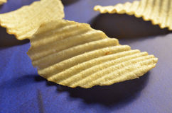 Potato chips with ridged or waves on blue surface. Ridged, rippled, or wavy potato chips on a deep blue surface Stock Images