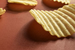 Potato chips with ridged or waves on brown surface. Ridged, rippled, or wavy potato chips on a brown surface Royalty Free Stock Photos