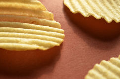 Potato chips with ridged or waves on brown surface. Ridged, rippled, or wavy potato chips on a brown surface Stock Image