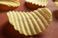 Potato chips with ridged or waves on brown surface. Ridged, rippled, or wavy potato chips on a brown surface Royalty Free Stock Images
