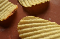 Potato chips with ridged or waves on brown surface. Ridged, rippled, or wavy potato chips on a brown surface Royalty Free Stock Photo