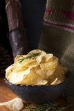 Potato chips with rosemary. On a wooden table Stock Photos