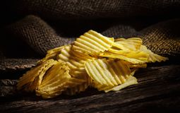 Potato chips on rustic wooden table Royalty Free Stock Images