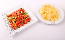 Potato Chips with salad. Goldy Potato Chips on white plate with salad stock photography