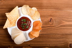 Potato chips with sauce in a plate on the table top view Royalty Free Stock Photo