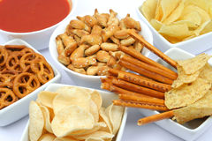 Potato chips and snacks. Potato chips, corn chips, pretzels and fish crackers in bowls, isolated on white Stock Photos