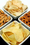 Potato chips and snacks. Potato chips, corn chips, pretzels and fish crackers in bowls, isolated on white Royalty Free Stock Photography