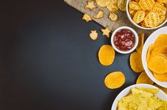 Potato chips and snacks on black slate table, top view Stock Photos