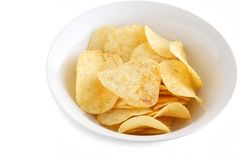 Potato Chips in a White China Bowl. A close up shot of some fresh potato chips in a white china bowl on white background royalty free stock image