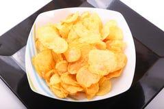 Potato Chips on white dish. Goldy Potato Chips on white plate above black dish Stock Photography