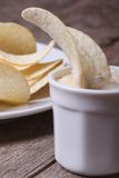 Potato chips in a white sauce macro. Vertical Stock Images