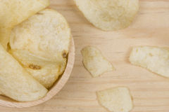 Potato chips in wood cup on wood table Stock Photos