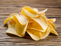 Potato chips on a wooden background. Royalty Free Stock Image