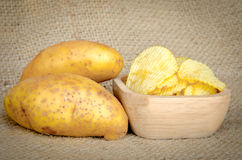 Potato chips in a wooden bowl and fresh potatoes. On sack background Royalty Free Stock Photo