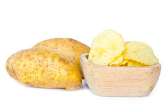 Potato chips in a wooden bowl and fresh potatoes Stock Images