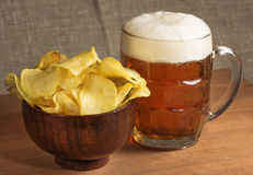Potato chips in a wooden bowl and mug of beer on the table Stock Images