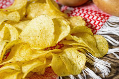 Potato chips. Potato chips on a wooden table. Fresh raw potatoes on the background Stock Image