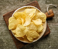Potato chips on wooden table Royalty Free Stock Image