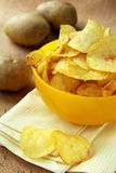 Potato chips in a yellow cup, and potato Royalty Free Stock Photography