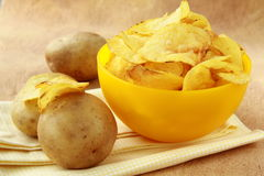 Potato chips in a yellow cup, and potato Stock Photography