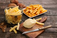 Potato on chopping board with a knife Stock Images