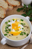 Potato cream soup with poached eggs Royalty Free Stock Images