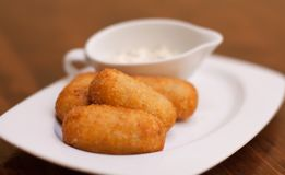 Potato croquettes with jamon and white saucepan in white plate. Brown blurred background. Selective soft focus. Photography stock photo
